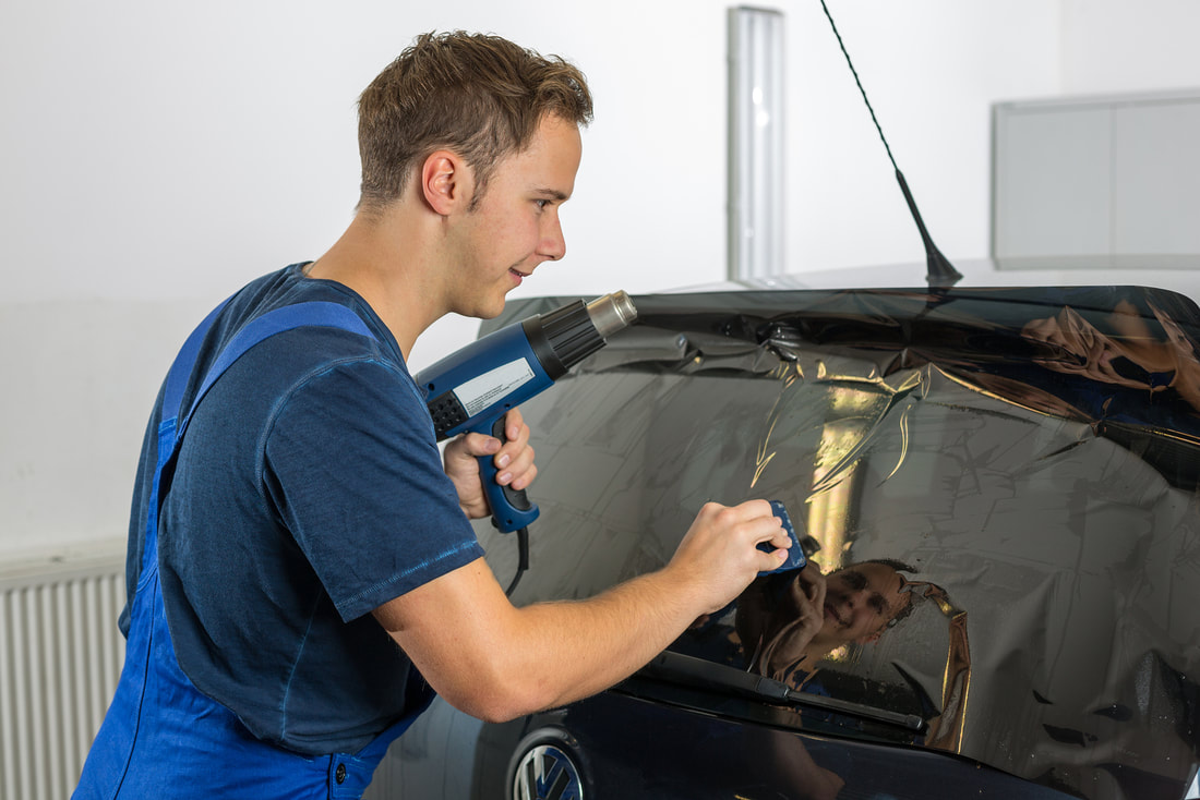 Young man applying window tint film to a car
